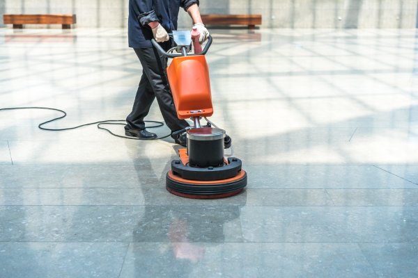 man cleaning a floor using a machine