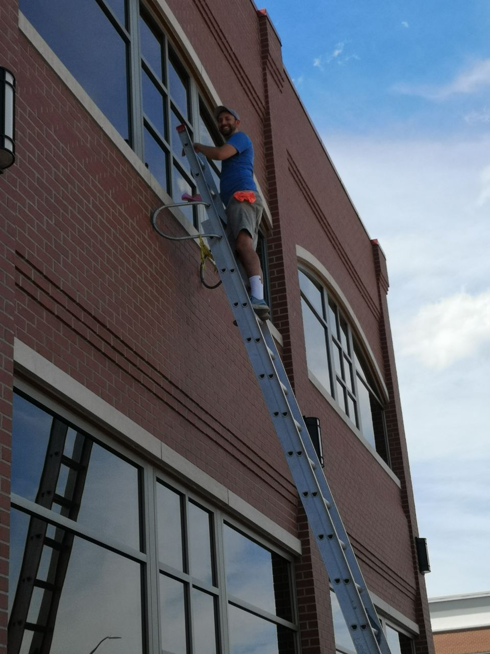 man cleaning exterior windows